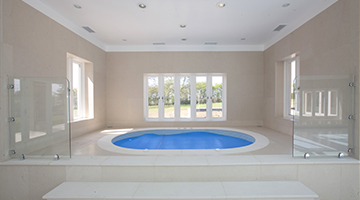 This pool design in Hatfield Heath included a raised spa area and some glazed screens to protect against possible falls from the young children